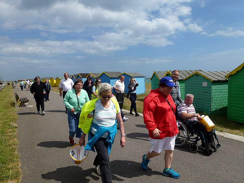 Photo of summer outing to the beach, walking by the beach huts